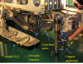 This photo shows model 5512 mounted to the PMM carriage with the towed, TPIV system in the foreground supported by the PMM carriage strongback. The underwater camera enclosures and laser-sheet generator (all submerged) are visible in the image.